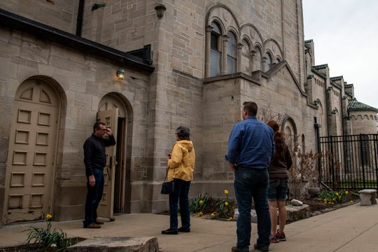 To prevent the spread of COVID-19, Bruce Behrens allows 10 people inside the church at a time during Holy Week confession at St. Philip Roman Catholic Church on Wednesday, April 8, 2020 in Battle Creek, Mich.