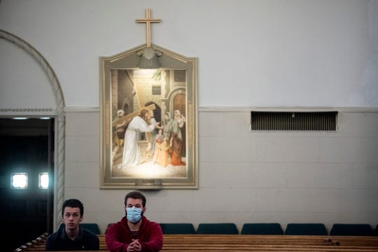 Brothers Sebastian and Michael Scriber attend Holy Week confession at St. Philip Roman Catholic Church on Wednesday, April 8, 2020 in Battle Creek, Mich. To prevent the spread of COVID-19, only 10 people are allowed inside the church at a time.