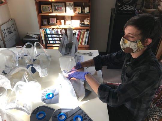 A Blackmouth Design employee sews a PAPR hood.