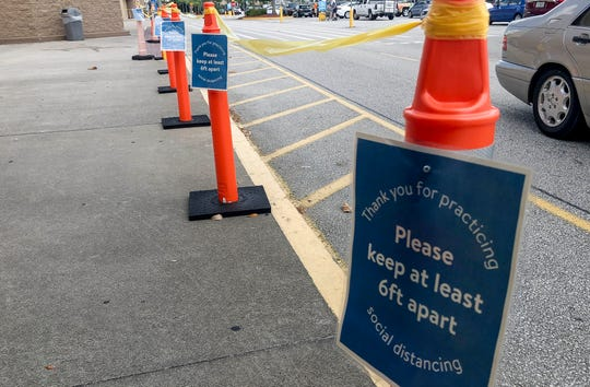 Signs every six feet outside the Walmart Supercenter in West Melbourne help shoppers maintain their social distancing when entering the store.