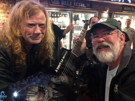 Gregg Wiggins of Indian Harbour Beach, right, looks forward to a time when he can grab a beer with friends. In pre-coronavirus days, he stopped by World of Beer in Viera for a beer and ended up winning guitar signed by musician Dave Mustaine, left, of Megadeth.