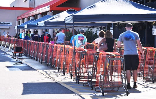 The new norm, social distancing and six feet apart. People lined up Tuesday morning at the Home Depot on Merritt Island. The store was limiting the amount of customers in the store at one time and people where lined up outside waiting to shop.