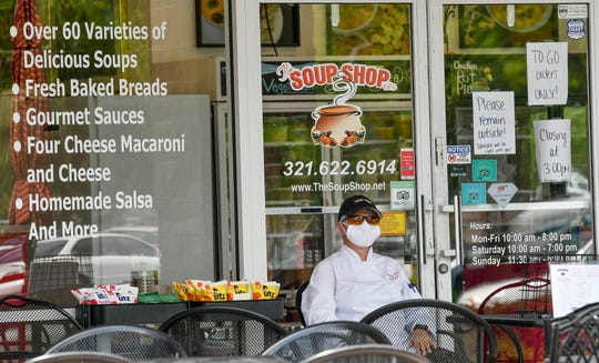 Andrea Lucas of The Soup Shop in Melbourne sits outside as she waits for takeout customers Thursday afternoon, April 9, 2020.