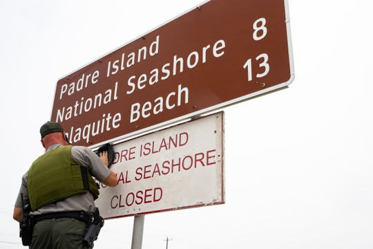 A National Park Ranger places a closed sign below the Padre Island National Seashore sign on Park Road 22 on Thursday, April 9, 2020. Nueces County Judge Barbara Canales ordered the vehicle access to parks and beaches closed over the Easter weekend.