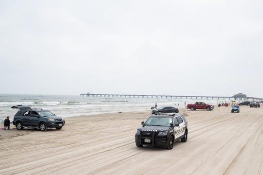 Police patrol the beach the beach near Bob Hall Pier on Thursday, April 9, 2020.