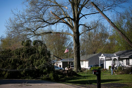 A man cuts up tree limbs on Betty Lane, in Milford, after storms came through the area on Wednesday evening.