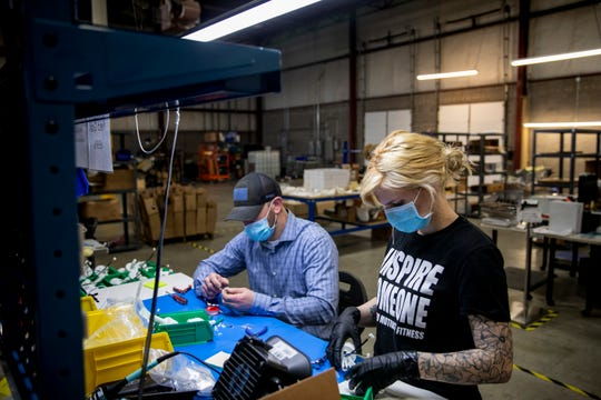 Hannah Week and Daniel Craig work on the electronic assembly for the PearlAqua Micros, the world's smallest UV disinfection system, at AquiSense Technologies on Tuesday, April 7, 2020 in Erlanger, Kentucky.