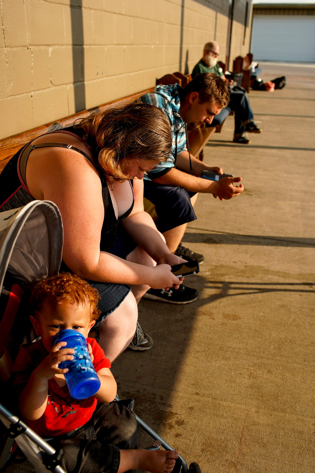 Amber Yoho leans over and takes part in a prayer with her son Aidyn Yoho, 1, in a stroller beside her at Manna Cafe Ministries in Clarksville, Tenn., on Wednesday, April 8, 2020.