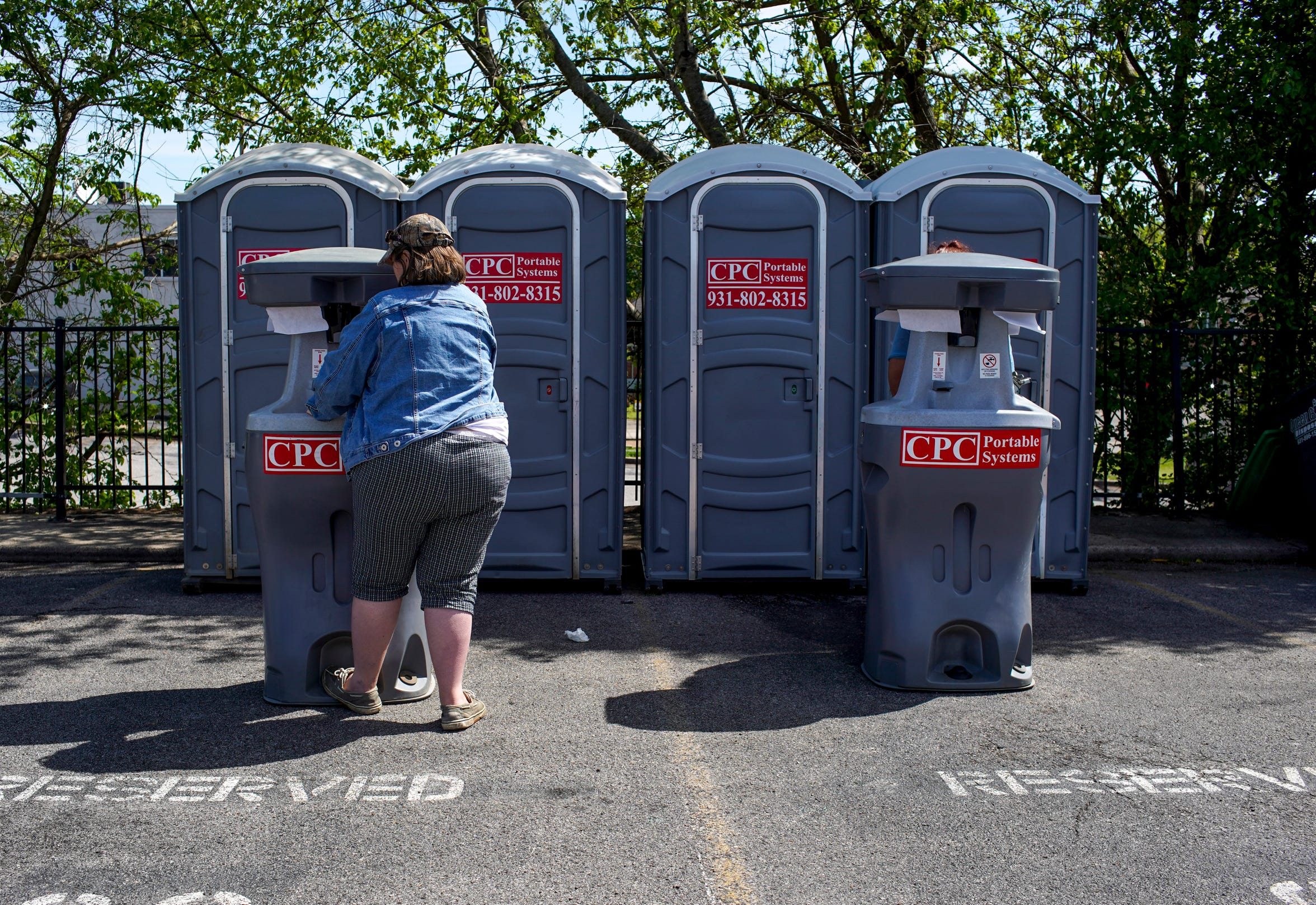Residents wash their hands after using port-a-potties at mobile hand washing stations with a water pump at the parking lot across the street from the Downtown Commons in Clarksville, Tenn., on Thursday, April 9, 2020.