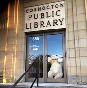A large teddy bear holds onto the door handle at the Coshocton Public Library, which is currently closed. Many businesses are participating in the Coshocton County Bear Hunt where children can spot stuffed animals around town.