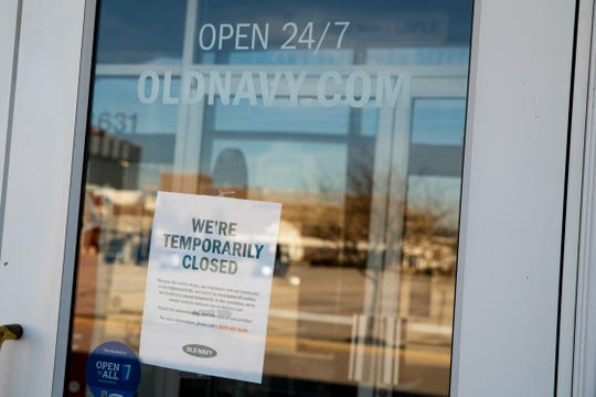The empty parking lot is reflected in the door of temporarily closed Old Navy store in Indianapolis on March 2. More than 6.6 million Americans applied for unemployment benefits the week of March 23.