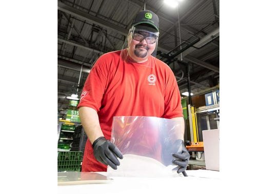Jerry Miller, an assembler at John Deere Seeding Moline, assembles protective face shields for health care workers.