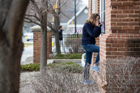 Judy Armbruster of Grosse Pointe Woods shows the mail that she brought as she talks to her mother Mary Lou Wholihan over the phone outside of Sunrise Senior Living in Grosse Pointe Woods, Friday, March 27, 2020.
