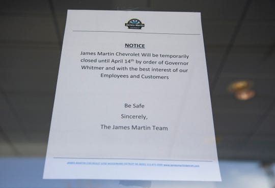 A sign at James Martin Chevrolet on Woodward Avenue in Detroit on April 9, 2020, tells customers that they will be closed until April 14 due to the risk of the Novel Coronavirus.