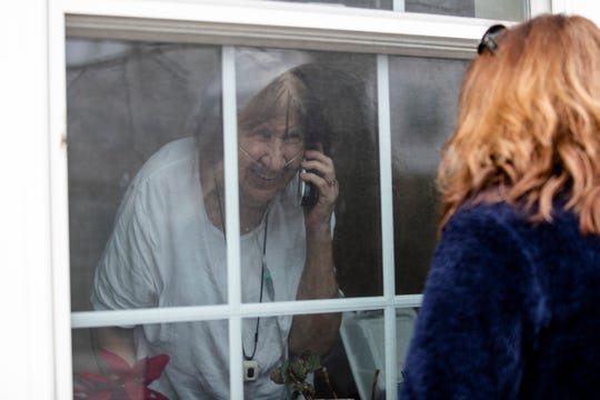 Judy Armbruster of Grosse Pointe Woods, right, talks to her mother Mary Lou Wholihan by the windows outside of Sunrise Senior Living in Grosse Pointe Woods, Friday, March 27, 2020.