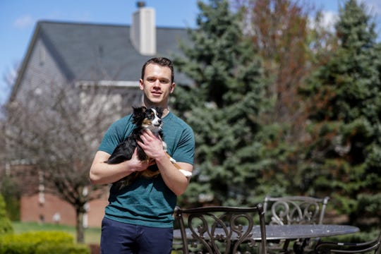 Andrew Dolenga, 22, is a senior at Michigan State University, where he is getting a degree in mechanical engineering. Dolenga holds his dog, Tucker, at his parent's home in Rochester, Michigan, on April 8. He is now taking his classes online, but is still forced to pay his rent for his off-campus apartment even though he longer resides there.