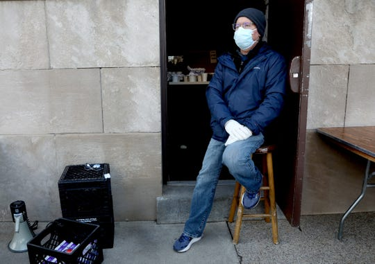 Father Tim McCabe of the Pope Francis Center in Detroit, Michigan on April 9, 2020. McCabe had spent part of his morning making sure the portable shower was working fine in addition to helping pass out food, milk and coffee to the lines of homeless looking for something to eat.