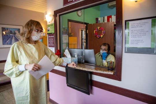 Registered nurse Lori Khaled stands by at Downriver Urgent Care as her husband, Dr. Mounir Khaled, fields a phone call on Thursday.