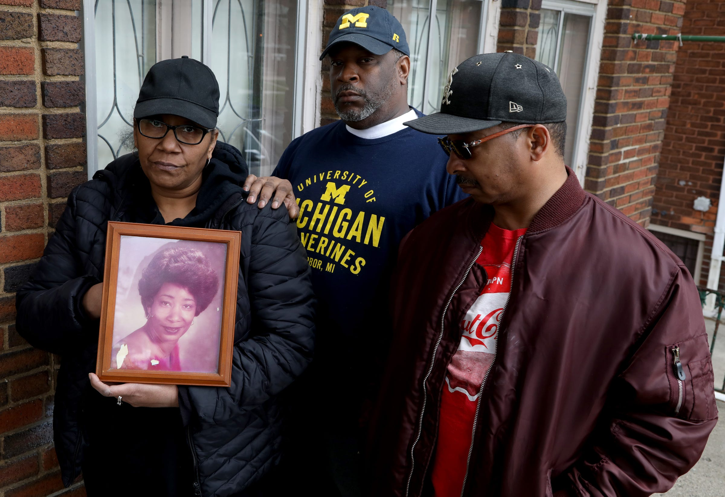 From left, siblings Carolyn Johnson, 51, of Eastpointe, Korey Hill, 46, of Detroit and Eric Burse, 53 of Detroit, with a portrait of their mother, Mildred Hill, who died April 7, 2020, after being diagnosed with COVID-19.