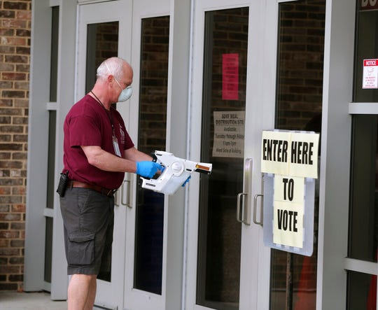 Jeff Knodl, facility foreman at Menomonee Falls High School, disinfect door handles at the high school as voters, ignoring a stay-at-home order over the coronavirus threat, cast ballots in the state's presidential primary election, Tuesday, April 7, 2020, in Menomonee Falls, Wis.