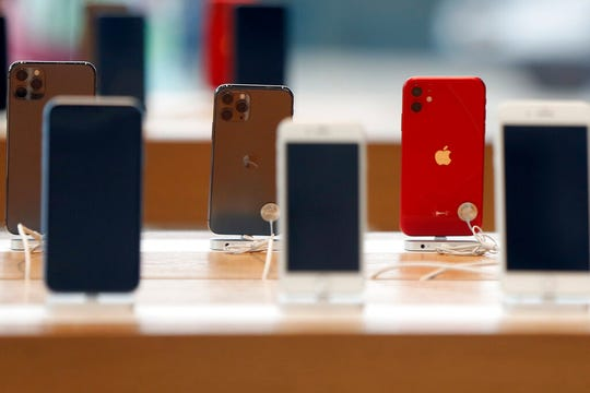 Rows of iPhones are displayed Saturday, March 14, 2020, inside a closed Apple store in downtown Brooklyn in New York.