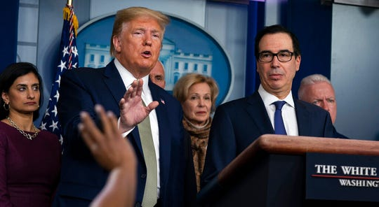 """In this March 17, 2020 file photo Treasury Secretary Steven Mnuchin, right, listens as President Donald Trump speaks during a press briefing with the coronavirus task force, at the White House in Washington.  Trump has been telling voters that the U.S. economy will leap back to life """"like a rocket,"""" stronger than ever after its bout with the coronavirus."""