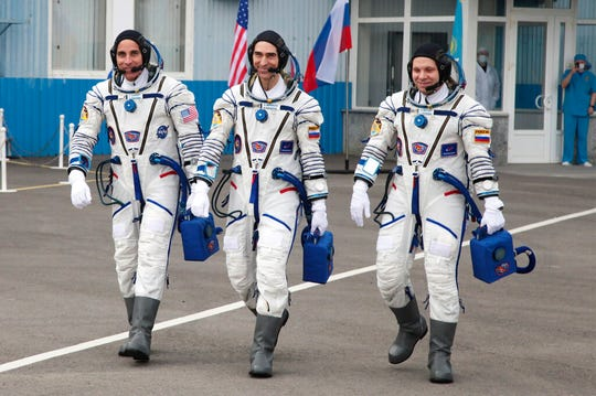In this handout photo released by Roscosmos Space Agency Press Service U.S. astronaut Chris Cassidy, left, Russian cosmonauts Anatoly Ivanishin, centre, and Ivan Vagner, members of the main crew of the expedition to the International Space Station (ISS), walk prior the launch.