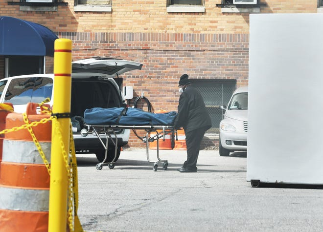 An employee for C.W. Morris Funeral Homes in Highland Park rolls out a body from Sinai-Grace on Thursday. The worker said it was a COVID-19 patient, but the funeral home denied it.