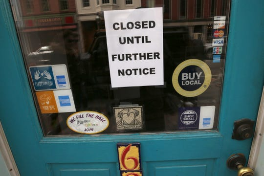 A closed sign hangs in the window of a shop in Portsmouth, N.H., due to caronavirus concerns.