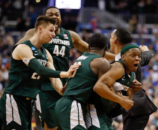 Michigan State guard Cassius Winston, right, celebrates with teammates Matt McQuaid (20), Nick Ward (44) and Gabe Brown (13) after defeating Duke in an NCAA East Regional in 2019.