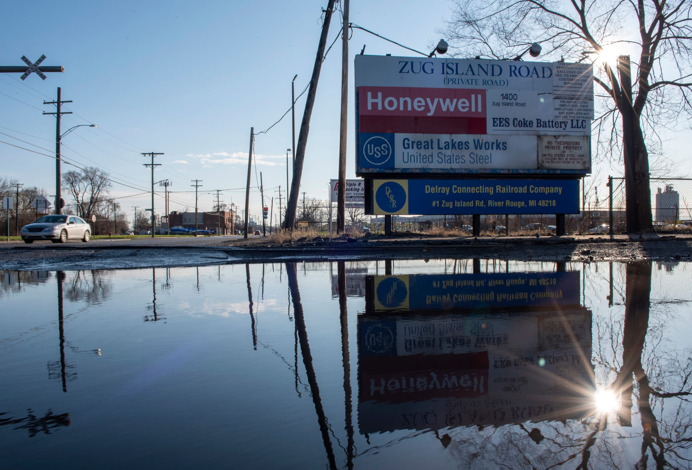 A modest sign along a pitted stretch of West Jefferson marks the entrance to Great Lakes Works on Zug Island in River Rouge. The Zug Island Road is reflected in a rain puddle, Thursday, April 9, 2020.