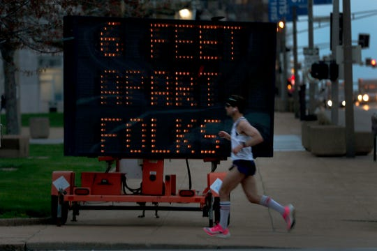 A person jogs past a sign encouraging social distancing last week in St. Louis.