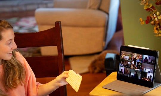 """Skylar Day, 18, holds up her matzah bread in front of the tablet's camera in her Newburgh, Ind., home so it can be seen by the other 100-plus participants in the """"virtual Seder dinner"""" hosted by a Florida family Wednesday evening, April 8, 2020. The Seder dinner is an annual tradition to mark the beginning of Passover for Jews across the world. The event had to become a virtual Seder because of the stay at home orders in place due to the COVID-19 pandemic. George Day opened his window, inviting others to share their special and meaningful religious observation."""