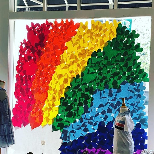 A rainbow made from colored hearts adorns the window at Hooray! children's boutique in Downtown Newburgh.