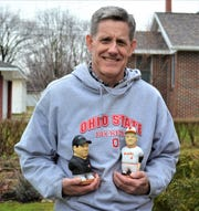 John Hoesman stands outside his Woodville home studio with two of his custom woodcarvings. Hoesman gained national attention when he was asked to create woodcarvings of the coaches during the 1996 Tostitos Fiesta Bowl.