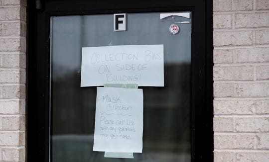 A sign at Wisconsin Face Mask Warriors' Green Bay distribution center directs volunteers to the collection area of its space at 1718 Velp Ave. in Green Bay.