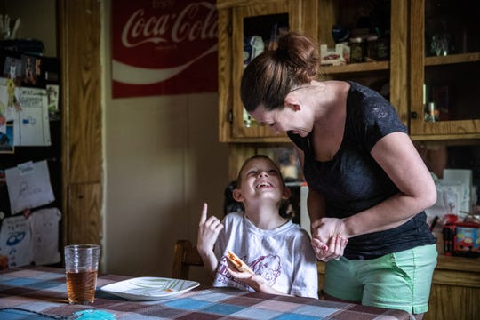 Stephanie Vaughn, a server at Applebee's who has been taken off the schedule as a result of the coronavirus outbreak, talks to her son Glenn Woods, 9, at he eats his lunch at their home in Fountain Inn Tuesday, April 7, 2020.