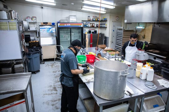 Samuel Servellon, and Ramses De La O, the executive chef at Larkin's, prep vegetables in the kitchen at their event space Thursday, April 9, 2020, as they prepare Easter meals to be picked up on Saturday.