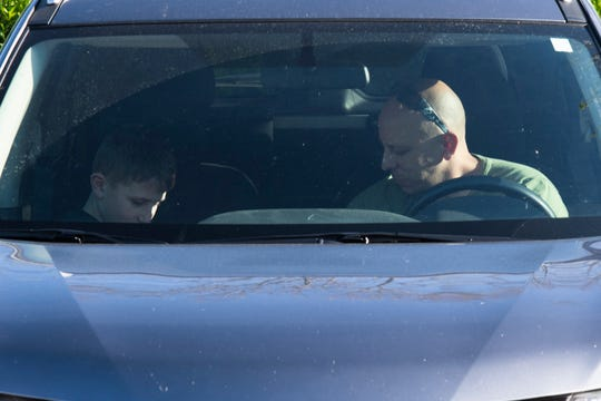 Ryan DeRosa, 11, and Deputy Mike DeRosa bow their heads during 20 minutes of prayer in the parking lot at Hillcrest Hospital in Simpsonville Thursday, April 9, 2020.