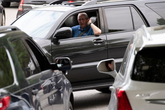 People say goodbye to each other from their cars after praying together in their cars in the parking lot at the Law Enforcement Center Wednesday, April 8, 2020.