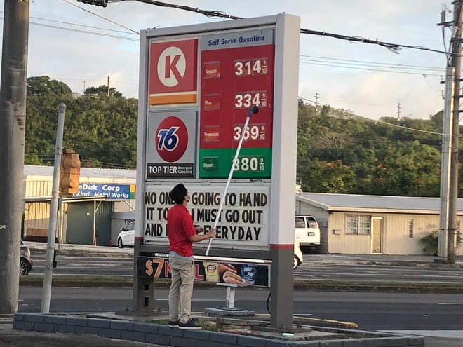 A 76 employee changes the signage at the Ypao Road 76 gas station on April 8, 2020. Regular unleaded gas dropped by 15 cents today to $3.15, which marks the eighth consecutive price drop.