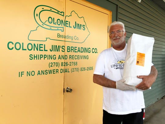 Mike DeLamar, owner of Henderson-based Colonel Jim's Breading Co., holds a 25-pound bag of breading outside his office. He is among the business people trying to navigate the ever-changing process of securing an emergency loan from the U.S. Small Business Administration to stay afloat while the COVID-19 pandemic has shut down many of his customers. (Photo by Chuck Stinnett)