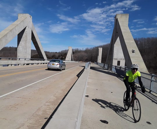 Mike Karnell of Coralville zips across the center span of Mehaffey Bridge, enjoying the wide, protected lane for bicyclists and hikers. Last year's opening of the Mehaffey Bridge Trail all the way from North Liberty to the Iowa River has increased safety for both motorists and bike riders.