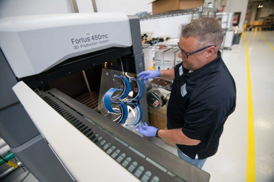 Andy Gossett, a technical support staff member at the UM Haley Barbour Center for Manufacturing Excellence, removes a batch of 3D-printed headbands from one of the facility's 3D printers. The headbands will be used for face shields by health care workers at Baptist Memorial Hospital-North Mississippi in Oxford during the COVID-19 pandemic.
