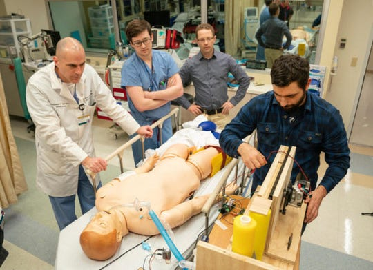 From left Fabien Maldonado, MD, Michael Lester, MD, and Robert Webster, Ph.D., help postdoc Joshua Gafford make adjustments to a homemade ventilator in the CELA Lab MRBIV third floor.  Engineering professor Robert Webster and postdoc Joshua Gafford created this homemade ventilator prototype in the hope that it can be made en masse to help relieve the shortage of ventilators due to COVID-19.