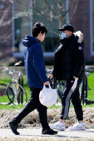 A person wears a mask as they walk across the Purdue University campus, Thursday, April 9, 2020 in West Lafayette.