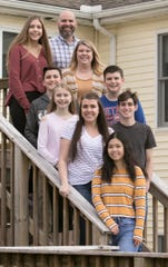 Foreign exchange student Cherry Sun from China stands in front of her host family, from top left, 15-year-old Lauren Martin, dad Daniel, Logan, 12, mom Jamie, Elizabeth, 10, Jake, 13, Brianna and Hunter.