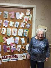 Bernice Schultz stands next to some of the 54 birthday cards she received from friends, family and many people she never met before.  She is in isolation at her assisted living facility in Owosso.