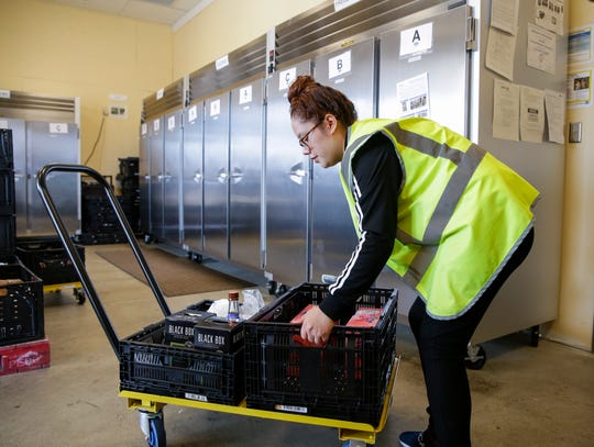 Maria Gonzalez arranges customers' pickup orders at Pick 'n Save at 250 West Holt Avenue.. There were orders for both pickup and delivery.