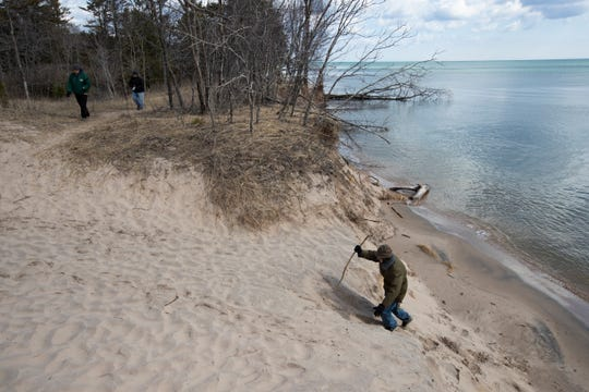 A man climbs a dune at Kohler-Andrae State Park in Sheboygan on Thursday. Gov. Tony Evers ordered the closing of 40 state parks beginning Thursday night until further notice.